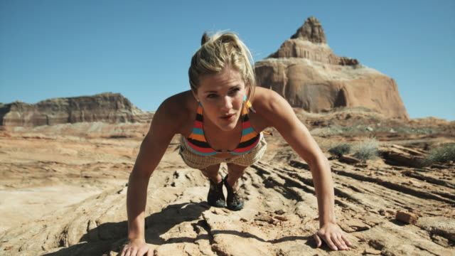 vídeos de stock e filmes b-roll de woman doing pushups in the desert - lago powell
