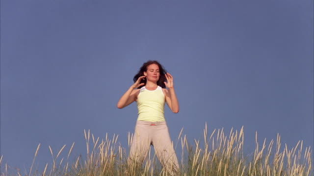 A woman doing Qigong by the sea Sweden.