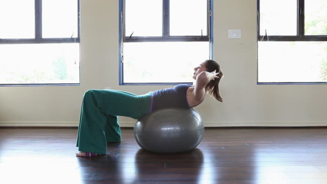 woman doing sit ups on pilates ball - pilates stock-videos und b-roll-filmmaterial