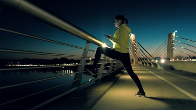 slo mo woman doing stretching exercises on a bridge at dusk - one mid adult woman only stock videos & royalty-free footage