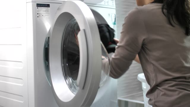 woman doing the laundry with washing machine at home - lavori di casa video stock e b–roll