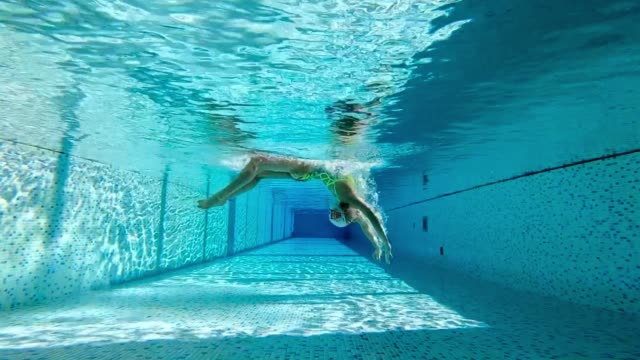 woman doing underwater somersault in swimming pool - the human body stock-videos und b-roll-filmmaterial