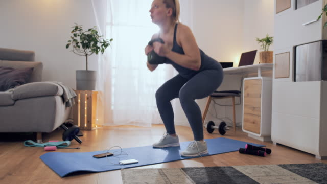 ds woman doing weightlifting exercises with a kettle - crouching stock videos & royalty-free footage