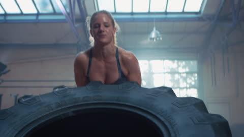 vidéos et rushes de femme de faire de l'exercice avec gros pneu - endurance