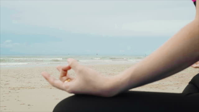 woman doing yoga and meditation on yoga mat. asian women wearing exercise clothes on beach in morning with sea and sky cloudy background. - slim stock videos & royalty-free footage