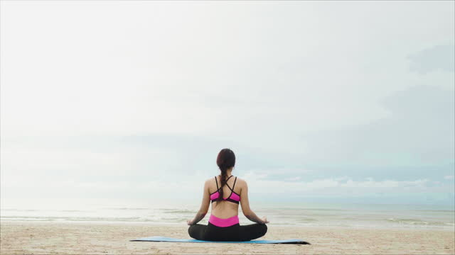 woman doing yoga and meditation on yoga mat. asian women wearing exercise clothes on beach in morning with sea and sky cloudy background. - leggings stock videos & royalty-free footage