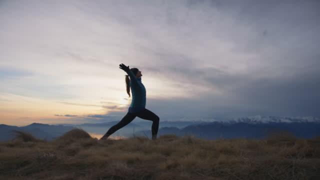 frau macht yoga bei goldenen stunden sonnenuntergang auf dem berggipfel - einzelne frau über 30 stock-videos und b-roll-filmmaterial