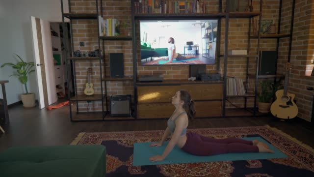woman doing yoga  at home with online teacher - yoga stock videos & royalty-free footage