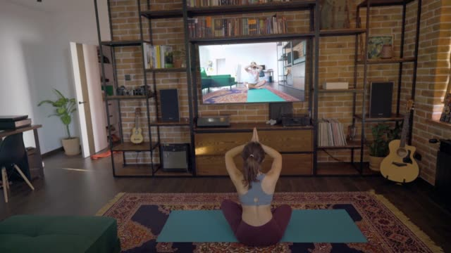 woman doing yoga  at home with online teacher - competition stock videos & royalty-free footage