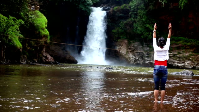 vídeos de stock e filmes b-roll de woman doing yoga body stretching exercise near waterfall - membro humano