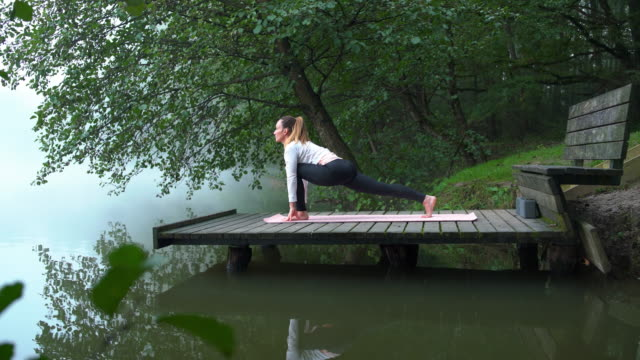 woman doing yoga by the lake on a misty morning - sun salutation stock videos and b-roll footage
