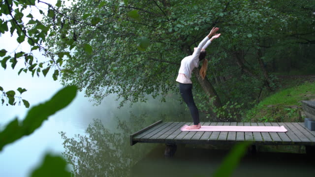 woman doing yoga by the lake on a misty morning - sun salutation stock videos & royalty-free footage