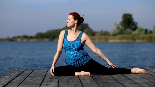 a woman doing yoga by the lake - tights stock videos & royalty-free footage