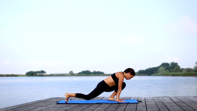 A woman doing yoga by the lake
