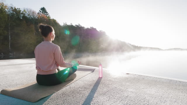 woman doing yoga exercised by the lake - determination stock videos & royalty-free footage