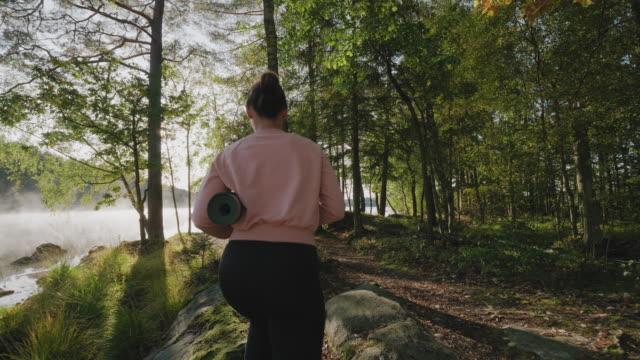 vídeos de stock e filmes b-roll de woman doing yoga exercises by the lake - atrás