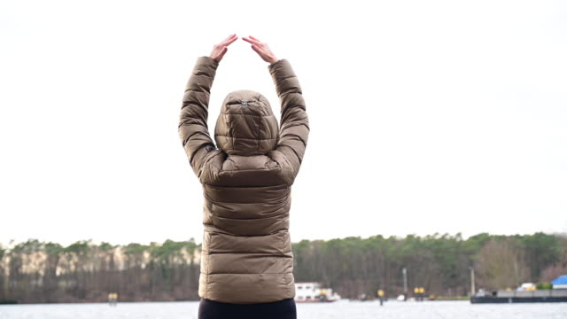 woman doing yoga exercises, meditation, balance with herself in a winter day on a lake. germany. brandenburg. - ウィンターコート点の映像素材/bロール
