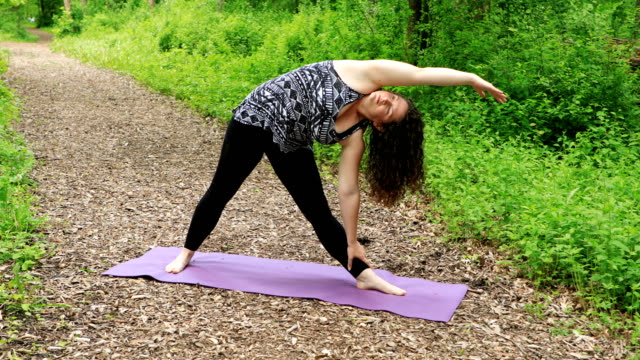 woman doing yoga - extended side angle pose - bending stock videos & royalty-free footage