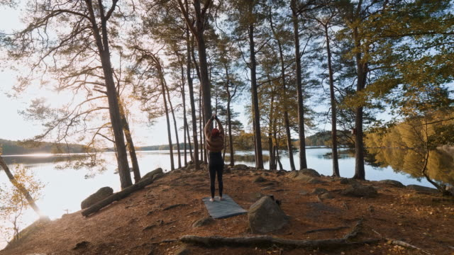 woman doing yoga in autumn woodland - sun salutation stock videos & royalty-free footage