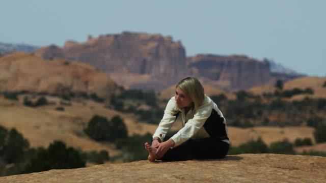 stockvideo's en b-roll-footage met woman doing yoga in the desert - bukken