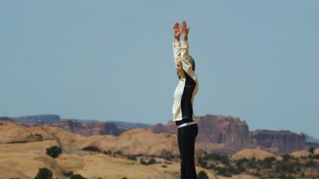 stockvideo's en b-roll-footage met woman doing yoga in the desert - menselijke arm