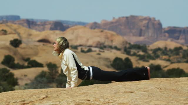 vídeos y material grabado en eventos de stock de woman doing yoga in the desert - de cara al suelo