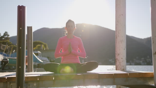 woman doing yoga, meditating on dock by the lake at sunset, view of mountains behind - posizione della preghiera video stock e b–roll