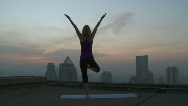 stockvideo's en b-roll-footage met ws pan woman doing yoga movements on rooftop / bangkok, bangkok, thailand - flexibiliteit