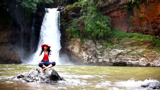 woman doing yoga near harvalem waterfall - postura video stock e b–roll