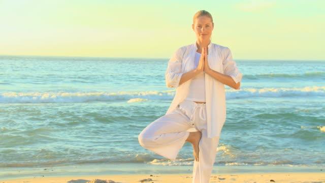 vídeos de stock, filmes e b-roll de woman doing yoga on a beach / cape town, western cape, south africa - pose de arvore