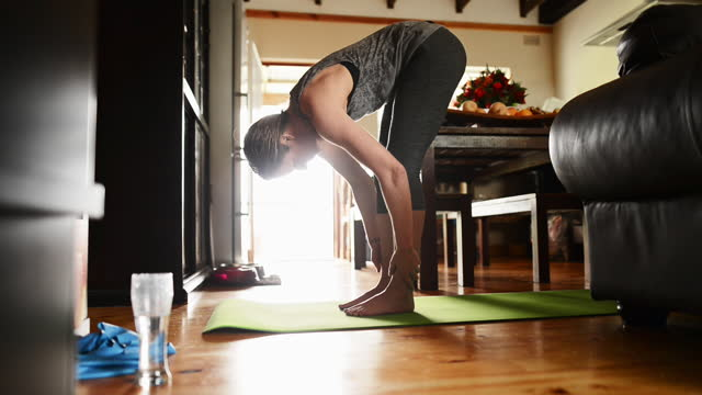 woman doing yoga on a mat in her living room - 40 44 years stock videos & royalty-free footage