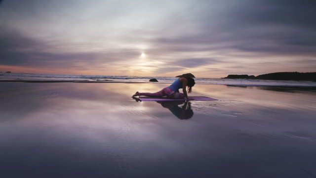 WS POV ZO Woman doing yoga on beach / Bandon, OR, United States