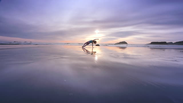 WS POV Woman doing yoga on beach / Bandon, OR, United States