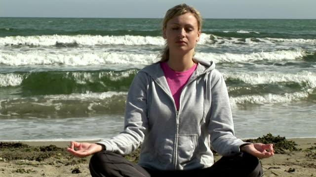 ms, woman doing yoga on beach, ireland - korslagda ben bildbanksvideor och videomaterial från bakom kulisserna