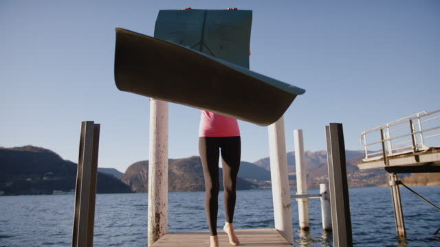woman doing yoga on dock at sunset, view of mountains and lake behind - clear sky stock videos & royalty-free footage