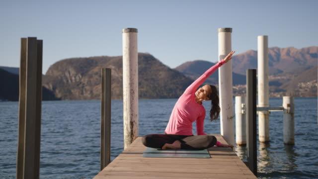 vídeos de stock, filmes e b-roll de mulher fazendo ioga no cais perto do lago ao pôr do sol, vista das montanhas atrás - rosa cor