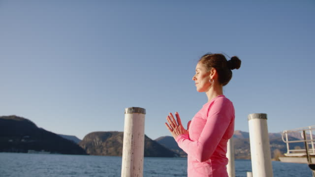 woman doing yoga on dock by the lake at sunset, view of mountains behind - part of a series stock videos & royalty-free footage