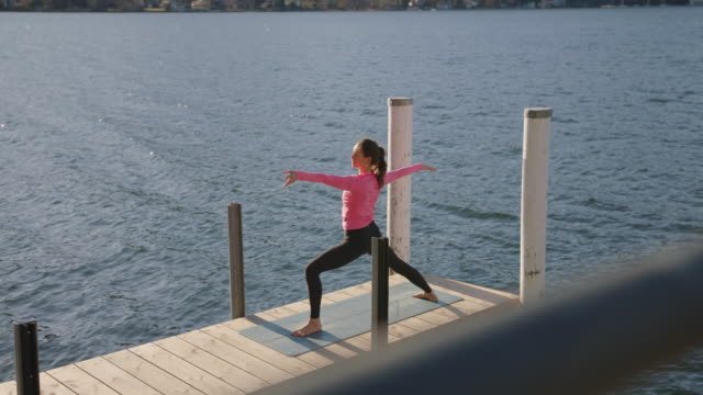 woman doing yoga on dock by the lake at sunset, view of mountains behind - 40 44 years stock videos & royalty-free footage