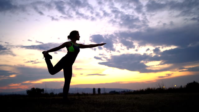 woman doing yoga on meadow - mindfulness stock videos & royalty-free footage
