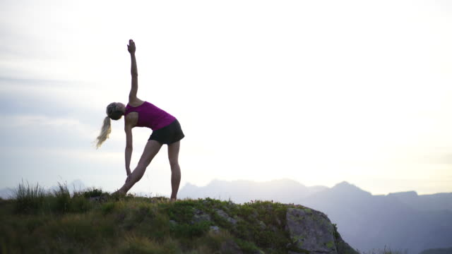 woman doing yoga on mountain top at sunset - mont blanc stock videos & royalty-free footage