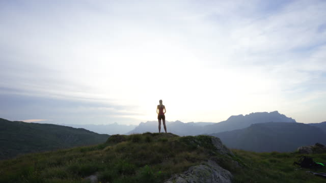 woman doing yoga on mountain top at sunset - arms raised stock videos & royalty-free footage