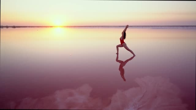 woman doing yoga  on pink salt lake in ukraine - majestic stock videos & royalty-free footage