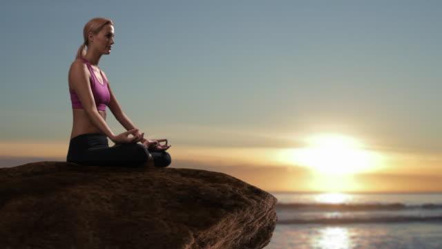 woman doing yoga on rock beside ocean/marbella region, spain - 若い女性だけ点の映像素材/bロール