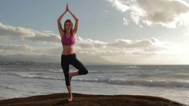 vidéos et rushes de woman doing yoga on rock beside ocean/marbella region, spain - rock face