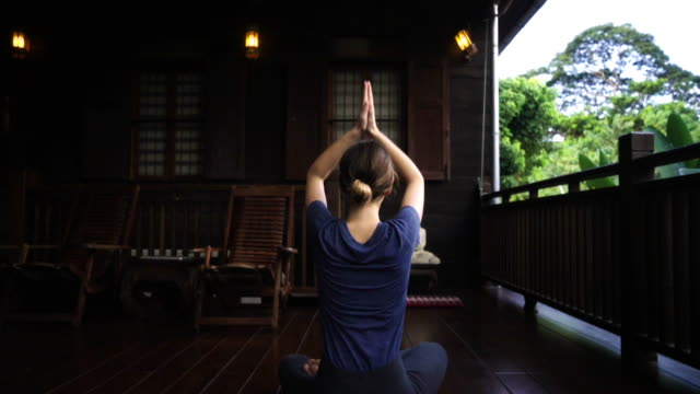 Woman doing yoga on the balcony