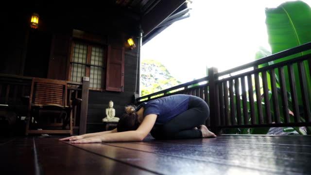 vídeos de stock, filmes e b-roll de mulher fazendo yoga na varanda - boa postura