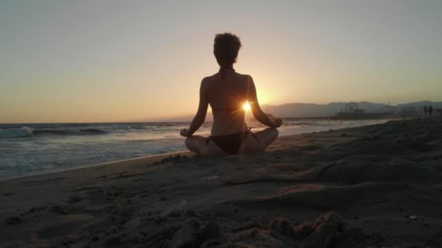 woman doing yoga on the beach at sunset - bikini stock videos & royalty-free footage