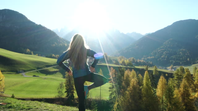 woman doing yoga overlooking valley and mountains at sunrise - early morning exercise stock videos & royalty-free footage