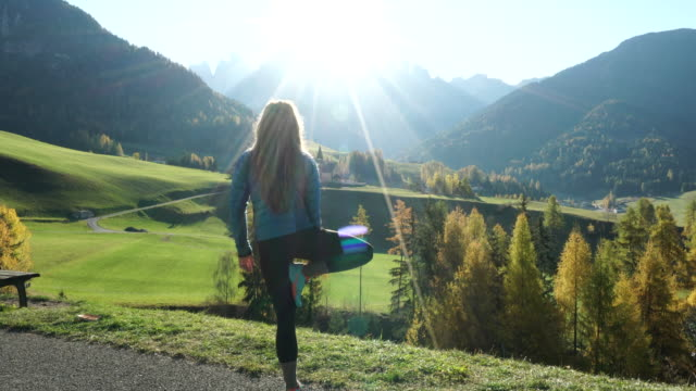 Woman doing yoga overlooking valley and mountains at sunrise