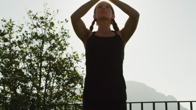 ms la woman doing yoga standing against sun / ravello,campania - only mid adult women stock videos and b-roll footage